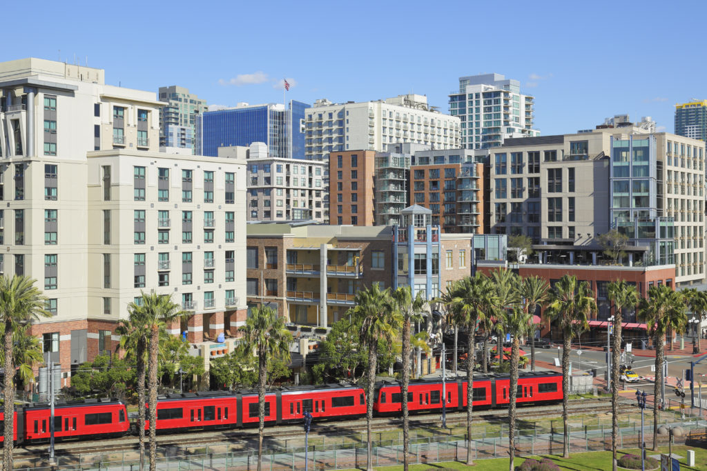 One of the red trolleys of the San Diego light rail system passes along the tracks located to the south of Gaslamp Quarter.